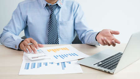 The businessman's hand sits at their desks and calculates financial graphs showing results about their investments, plan a successful business growth process. Stock fotó