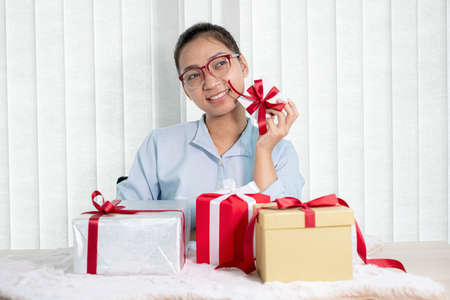 Asian woman holding a gift box Glad to be the giver of surprise with excitement, joy, and smiles on the holidays, Christmas, birthdays, or Valentine's Day concept. Stock fotó