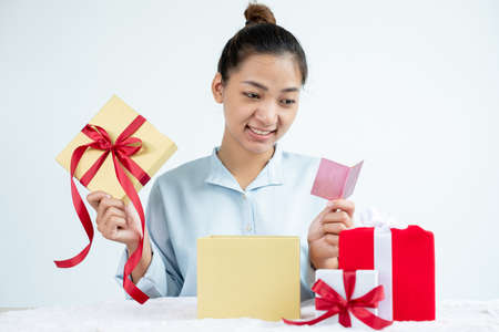 Asian women happy to open surprise boxes are stunned with excitement, joy, and smile on holidays, Christmas, birthday, or Valentine's Day concept. Stock fotó
