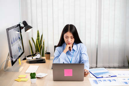 Asian woman working on a laptop with a cheerful and happy smile while working at the office.
