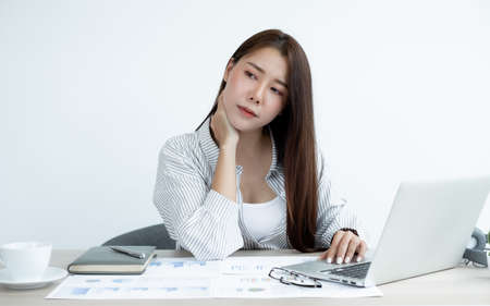 Asian women are tired from work, sit in a chair, stretch and massage neck, arm, shoulder For relaxation while working hard at the office. Standard-Bild