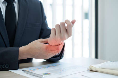 Businessman grasping the painful wrist caused by prolonged work on a laptop keyboard. Wrist numbness Arthritis While working at the office.