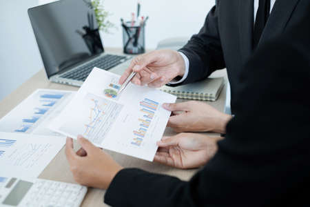 Two business leaders talk about charts, financial graphs showing results are analyzing and calculating planning strategies, business success building processes. Stock fotó