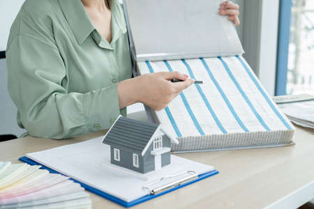 The designer is planning the interior of the house, illustrating and choosing the perfect colors for the new home with sample materials on the desk. Real estate design business Ideas.