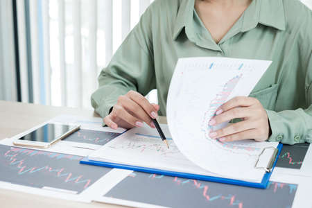 Hand of businesswoman are planning business investments related to shares By analyzing and calculating the stock market for marketing profits.