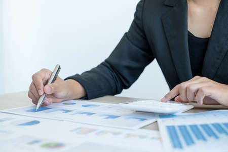The hand of an accountant woman is analyzing and calculating the financial graph showing the results in the office. Stock fotó