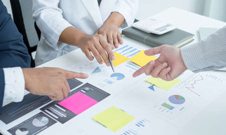 Three business leaders talk about charts, financial graphs showing results are analyzing and calculating planning strategies, business success building processes.