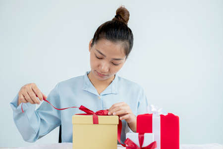 Asian women happy to open surprise boxes are stunned with excitement, joy, and smile on holidays, Christmas, birthday, or Valentine's Day concept.