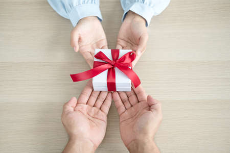 A hand holding a gift box Glad to be the giver of surprise with excitement, joy on the holidays, Christmas, birthdays, or Valentine's Day concept. 版權商用圖片