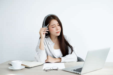 Video call, a young Asian woman wearing headphones, communicates via online video long distance, looking at the digital laptop screen, happily greeted with a friend.