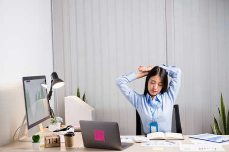 Asian female accountant is tired from working in a chair, stretching to relax and relax while working hard at the office.