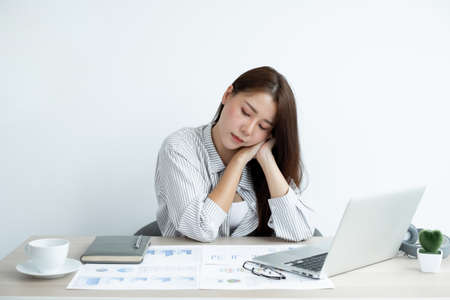 Working Asian women feel stressed, tired from work, migraine headaches from hard work while working at the office. Zdjęcie Seryjne