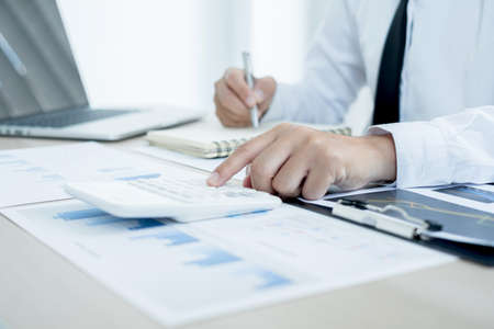 The businessman hand sits at their desks and calculates financial graphs showing the results of their investments planning the process of successful business growth.