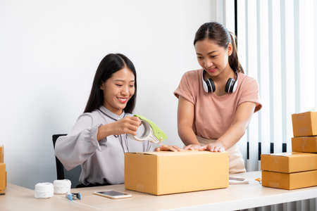 An Asian businesswoman, two owners with lots of boxes on their desks, happy to sell online, take orders from customers, and arrange their mail delivery.