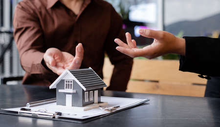 A real estate agent with a House model is talking to clients about buying home insurance. Home insurance concept.