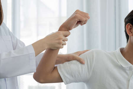Female physiotherapists provide assistance to male patients with elbow injuries examine patients in rehabilitation centers. Rehabilitation physiotherapy concept.