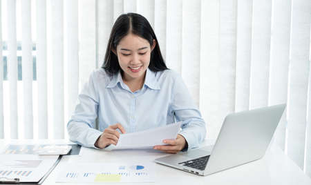 Asian female accountant sits at their desks and calculates financial graphs showing results about their investments, plan a successful business growth process. Stock fotó