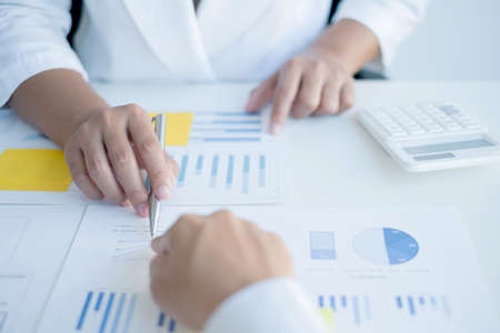 Two business leaders talk about charts, financial graphs showing results are analyzing and calculating planning strategies, business success building processes.