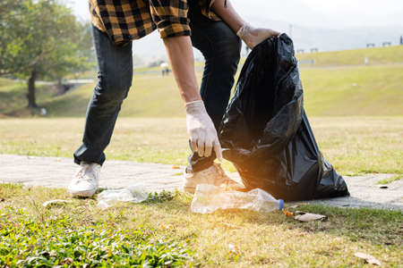 Man's hands pick up plastic bottles, put garbage in black garbage bags to clean up at parks, avoid pollution, be friendly to the environment and ecosystem.