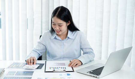 Asian female accountant sits at their desks and calculates financial graphs showing results about their investments, plan a successful business growth process.