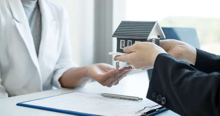 Real estate agent broker hand over the home to the new owner after completing the signing according to agreement renting a house and buy house insurance Home insurance concept.