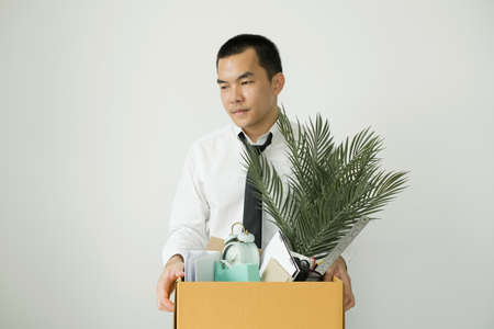 Asia businessman is upset by dismissal in packing belongings company into cardboard box Young man stress disappointed by Dismissal. From crisis economic scrap.