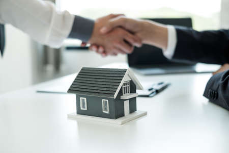 Businessmen and brokers' real estate agents shake hands after completing negotiations to buy houses insurance and sign contracts. Home insurance concept.