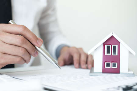 Agents working in real estate investment Hold the key home Ready home insurance signing contracts in accordance with the home buying insurance agreements approving purchases for clients.