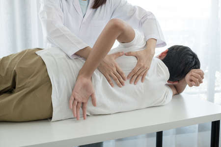 Female physiotherapists provide physical assistance to male patients with back injuries back massages for relaxation and muscle recovery in the rehabilitation center. Reklamní fotografie