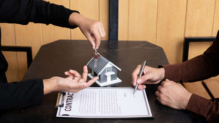 A real estate agent broker hand over the house key to the new owner after completing the signing according to the agreement renting a house and buy the house insurance.
