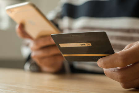 The businesswoman's hand is holding a credit card and using a smartphone for online shopping and internet payment.