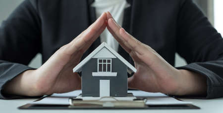 The house is covered by the hands of a real estate agent to protect the house for customers, homebuyers, insurance, ready give to with new owner. Real estate Home insurance concept. Reklamní fotografie