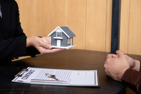A real estate agent gives the house to a new owner's client after completing the signing of the lease and formally completing home insurance. Rental and insurance concepts.