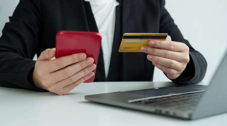 The businesswomen's hand is holding a credit card and using a smartphone for online shopping and internet payment in the office.