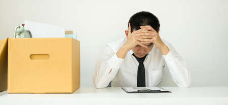 A man office worker is unhappy with being fired from a company packing things into cardboard boxes. The young man was stressed and disappointed by being fired. concept of layoffs and unemployment.