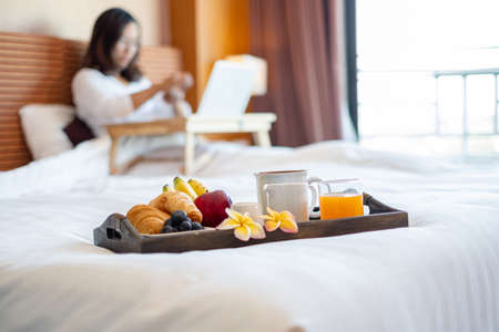 Focus on sweets fruit. Young Asian women smiling happily at freelance work, working on a notebook while relaxing in bed with snacks and fruit in a hotel room. Vacation and relaxation. Reklamní fotografie