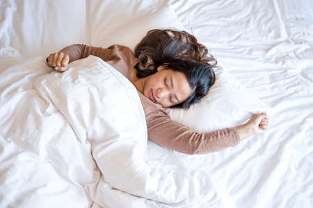 A young Asian woman sleeps comfortably in a hotel room with a happy face. It is a good rest during the long holidays. Top view.