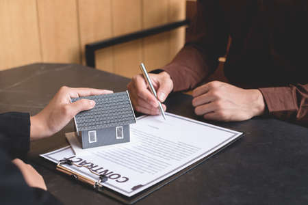 A real estate agent with a house model is talking to clients about buying home insurance and having customers sign contracts under the formal contract agreement. Home rental and insurance concept.