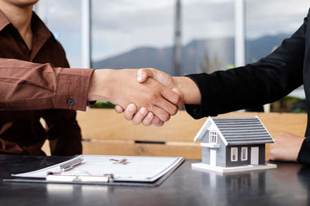 Businessmen and brokers real estate agents shake hands after completing negotiations to buy houses insurance and sign contracts. Home insurance concept. Reklamní fotografie