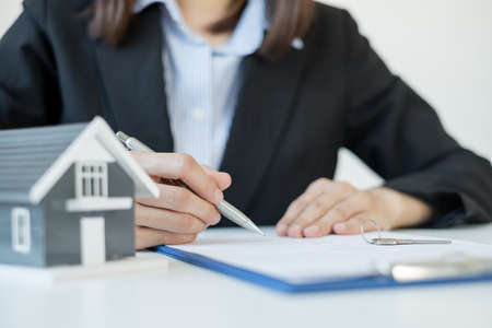 agents working in real estate investment and home insurance signing contracts in accordance with the home buying insurance agreements approving purchases for clients.