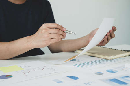 work from home, The hand of a man who works in finance sits at his desk at home and calculates financial graphs showing the results of his investments, planning the steps of his business growth.