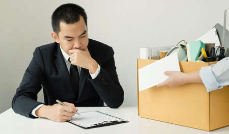 Desperately fired female office worker employee hands her employer her resignation letter and packs her belongings in a cardboard box concept dismissal and unemployment.