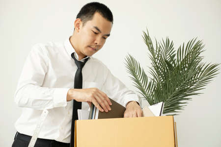 A male office worker is unhappy with being fired from a company packing things into cardboard boxes. The young man was stressed and disappointed by being fired. concept of layoffs and unemployment.