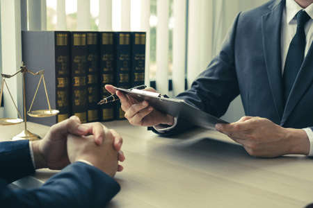 Male lawyers or a judge counseling clients about judicial justice and prosecution with scales, judges gavel, legal documents legal services concept.