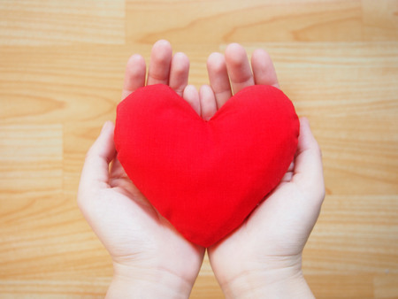 fibrillation: Female hands holding red heart on wooden background. Love or Healthcare and Medical concept.