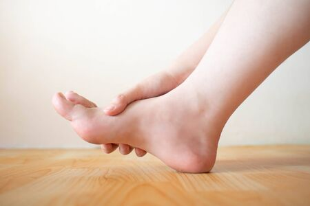 Young female suffering from foot pain or numbness at home. Causes of pain include plantar fasciitis, gout, arthritis, tendinitis, diabetic neuropathy or overuse injuries. Healthcare concept. Close up.