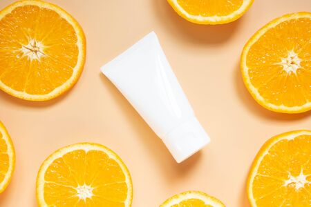 Natural vitamin c skincare products w/ fresh juicy orange fruit slice on orange background. Cosmetic beauty product branding mock-up for moisturizing cream, lotion, foam or shampoo. Top view.