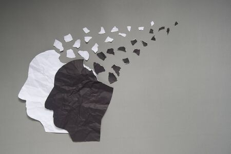 Bipolar disorder presented by human head made from black&white crumpled paper torn on gray background w/ copy space. Manic and depress emotion. Mental health, brain disorder and psychological concept.