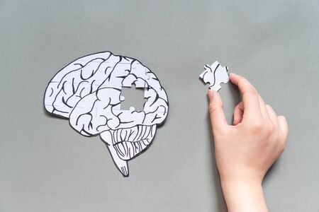 Female hand trying to connect a missing jigsaw puzzle of human brain on gray background. Creative idea for solving problem, memory loss, dementia or Alzheimer's disease concept. Mental health care.