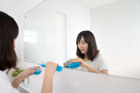 Young asian woman pouring mouthwash from bottle into glass in front of mirror bathroom. Oral hygiene routine for freshness breath, prevent plaque and gum disease. Dental health care concept. Фото со стока